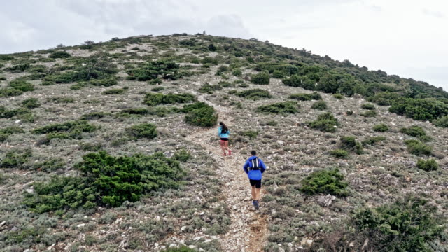 AERIAL Following a couple running up the rocky mountain trail in the Mediterranean