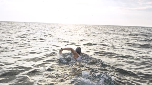 slo mo following a female open water swimmer - determination stock videos & royalty-free footage