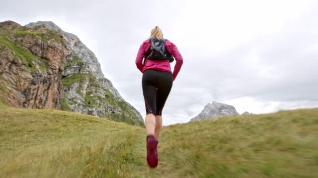 Following a female runner running on a grassy trail of a high mountain ridge