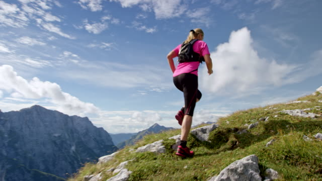 slo mo following a female runner running up a high mountain ridge in sunshine - top garment stock videos & royalty-free footage