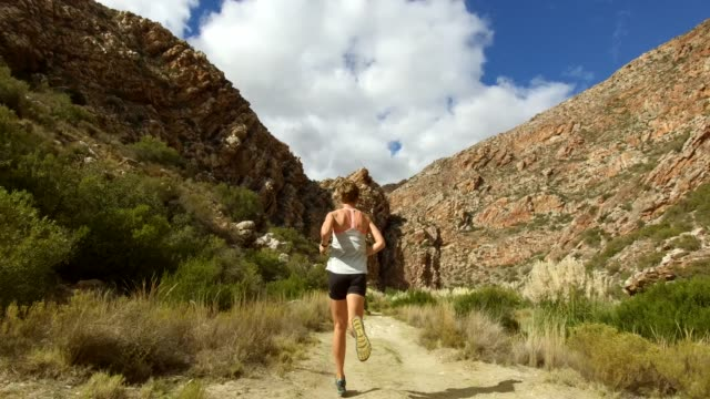 following a fit female runner along the river trail - hill stock videos & royalty-free footage