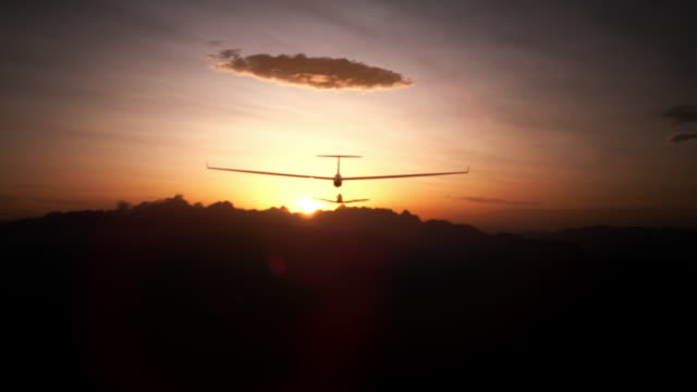 following a glider plane into sunset - glider stock videos & royalty-free footage