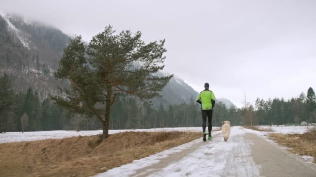 Following a man and his dog on a morning run on a snowy walkway in nature
