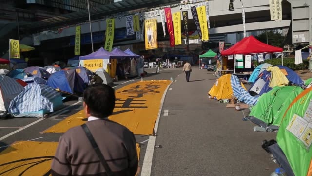 vídeos de stock, filmes e b-roll de pov following a pedestrian walking past tents tents and banners on connaught road central outside the central government offices in the admiralty... - ilha de hong kong
