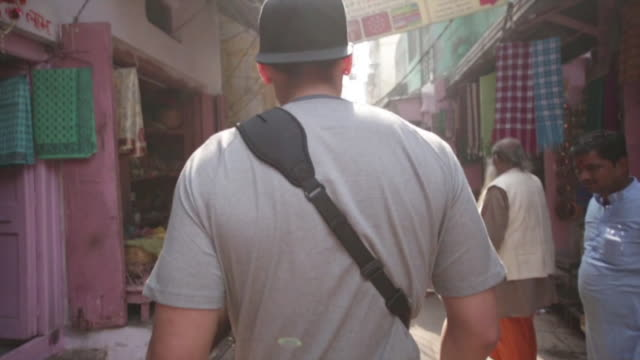 following a traveler through the varanasi market: slo mo - tourist stock-videos und b-roll-filmmaterial
