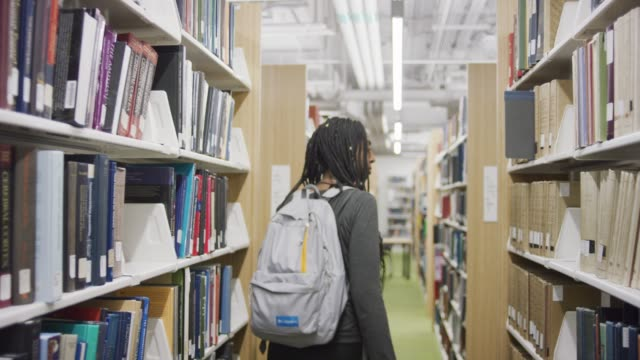 seguire una donna in cerca di libri in una biblioteca - studente universitario video stock e b–roll