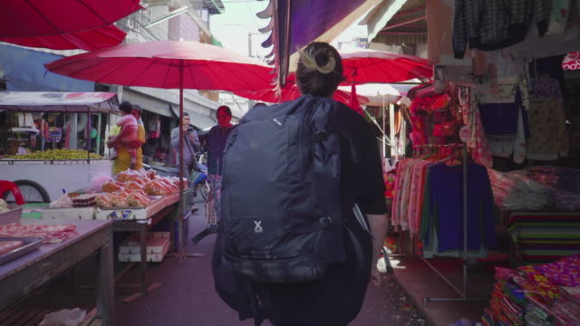 following a woman walk through an asian marketplace - zaino da montagna video stock e b–roll