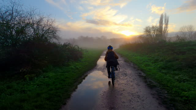following a young boy as he cycles towards a misty sunrise - one boy only stock videos & royalty-free footage