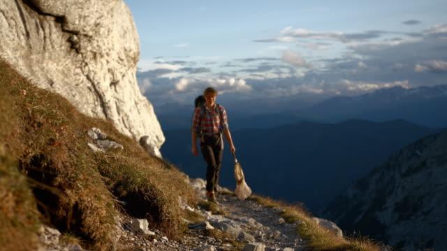 following a young female hiker on the side of a mountain - endast unga kvinnor bildbanksvideor och videomaterial från bakom kulisserna
