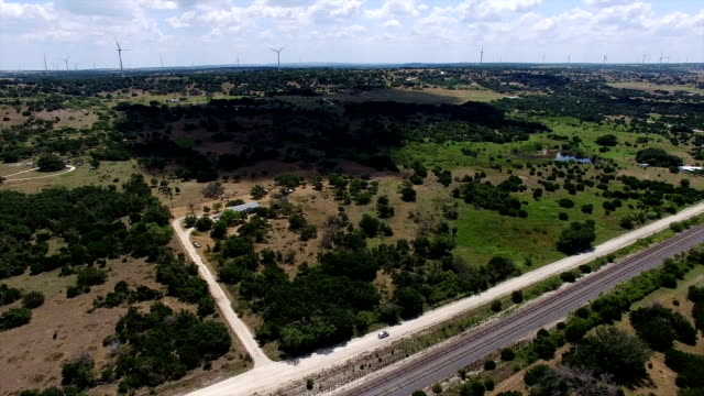 AERIAL: Following along Dirt Road Texas Hill Country Ranch property and Wind Farms