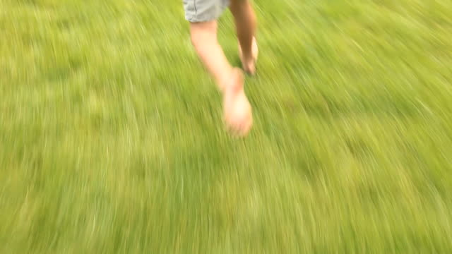 POV Following barefoot boy (4-5) running on grass, low section, Flagstaff, Arizona, USA
