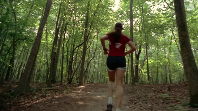 Following behind woman running on trail through woods / Red Top Mountain State Park, Georgia