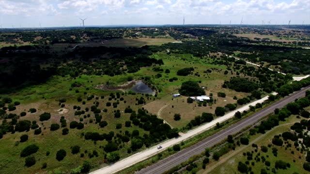 vídeos y material grabado en eventos de stock de después de coche conduciendo por camino de tierra en el país trasero texas ranchos con parque eólico en la distancia - rancho