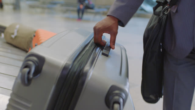 following checked luggage as african-american businessman grabs it off conveyor belt in baggage claim. - bagaglio video stock e b–roll