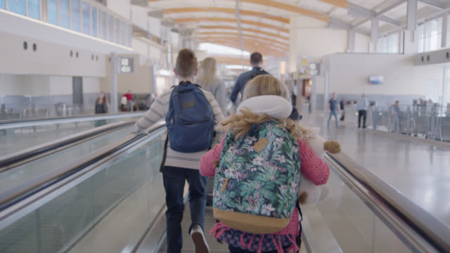following family of four as they run down moving walkway towards airport gate. - vacations stock videos & royalty-free footage