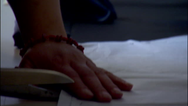 following female arms hands w/ bracelets cutting dark fabric around pattern reframing textiles sewing garments seamstress tailor - tailor stock videos & royalty-free footage