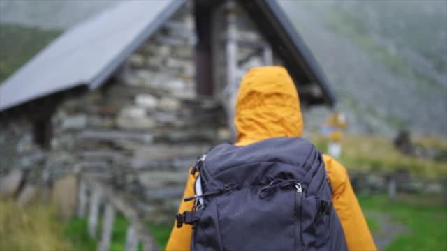 vídeos y material grabado en eventos de stock de después de que la excursionista camina hacia la cabaña de piedra en clima lluvioso - mochila bolsa