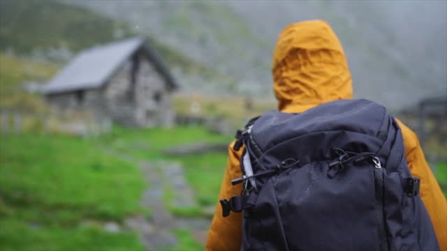 following female hiker walking towards stone hut in rainy weather - rucksack stock videos & royalty-free footage