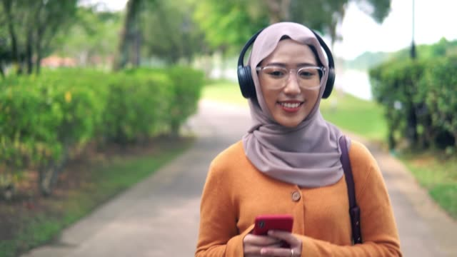 following front shot of beautiful asian girl listening to podcast at park - listening stock videos & royalty-free footage