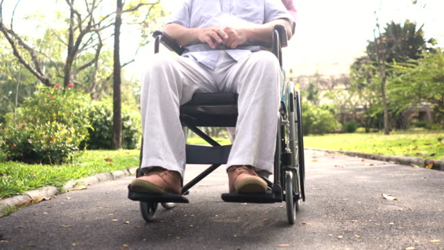 following front view: foot of senior husband while his wife bring him walk in park - wheelchair stock videos & royalty-free footage