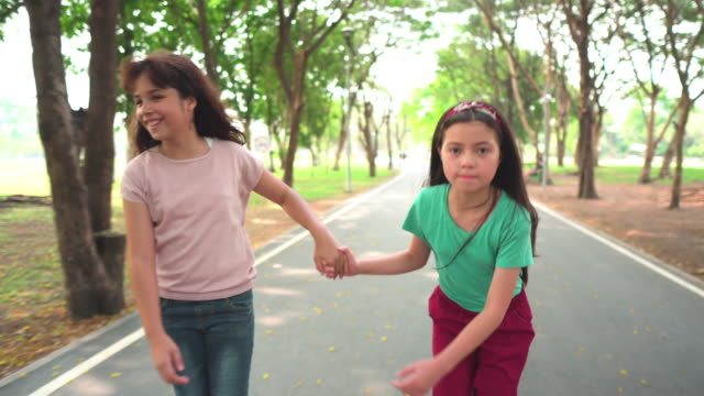 following front view: happy teenager girl and friend playing roller skate in public park in morning of weekend - pre adolescent child stock videos & royalty-free footage
