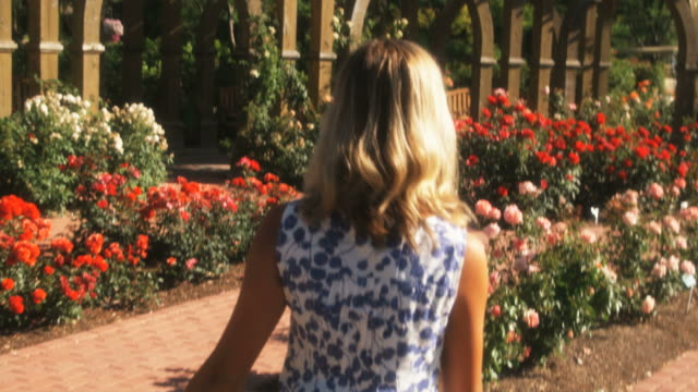 vídeos de stock, filmes e b-roll de slo mo pov following happy young woman walking through summer garden, lehi, utah, usa - lehi