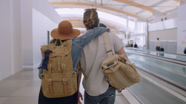 following hip young woman as she puts arm around boyfriend walking through airport terminal. - couple relationship video stock e b–roll