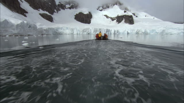 POV, PAN, Following inflatable raft approaching snow capped mountains, Paradise Bay, Antarctica