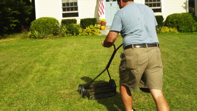 POV Following man using push lawn mower in front yard of house, Manchester, Vermont, USA