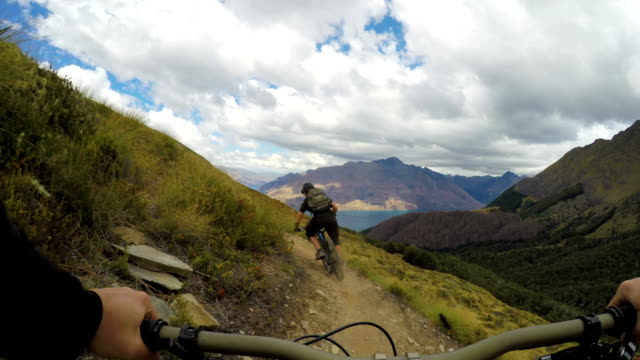 pov following mountain biker down mountain trail - mountain biking stock videos & royalty-free footage