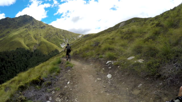 POV following mountain biker down mountain trail