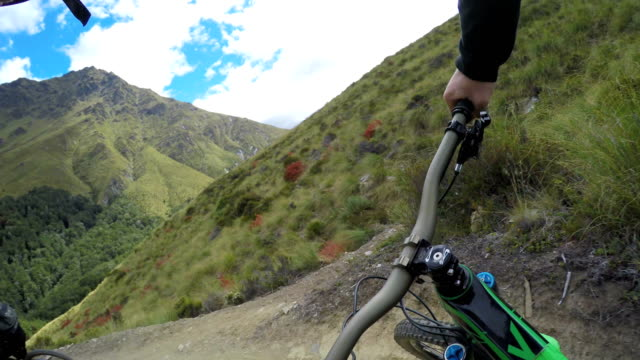 pov following mountain biker down mountain trail - mountain biking stock videos & royalty-free footage