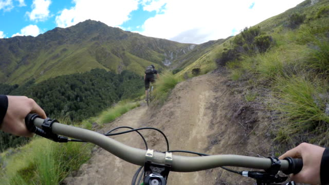 pov following mountain biker down mountain trail - andare in mountain bike video stock e b–roll