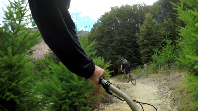 pov following mountain biker down mountain trail - mountain bike stock videos & royalty-free footage