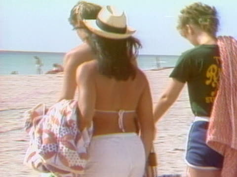 vídeos de stock, filmes e b-roll de following of four young people walking on a sandy beach. - toalha de praia