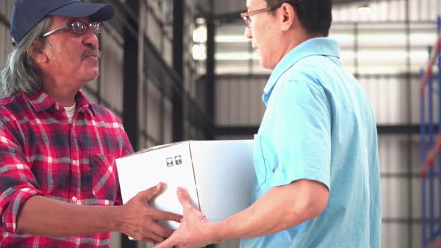 vidéos et rushes de suivant sur le corps de l'entrepôt senior travailleur asiatique a reçu la livraison, l'expédition de nombreuses boîtes en carton d'une voiture avec un travailleur postal avec des émotions positives sentiment et le bonheur qui envoie des paquets  - carrying