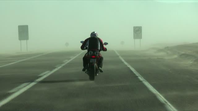 POV Following person riding motorbike through desert landscape, Calama, El Loa, Chile