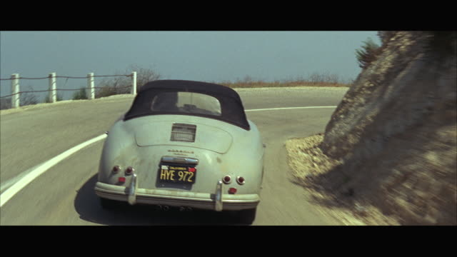 1966 pov following porsche sports car driving down mountain road - 1966 stock videos and b-roll footage