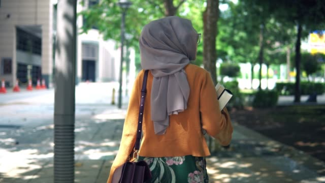 following rear shot of young asian girl walking with book outdoor - hijab stock videos & royalty-free footage