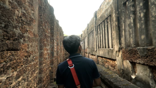 following rear view: young traveler is walking among stone wall of wat si mahathat chaleang - maze stock videos & royalty-free footage