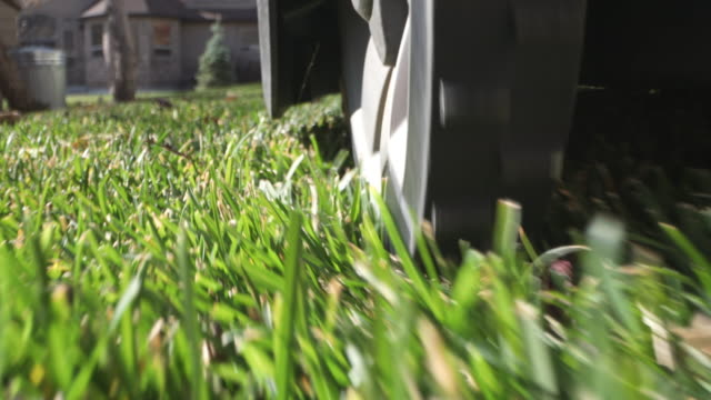 following robot lawn mower as it trims the grass from behind the wheel - grass stock videos & royalty-free footage