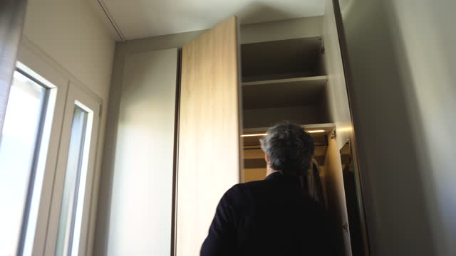 following shot of a man wearing black opening a closet - cabinet stock videos & royalty-free footage