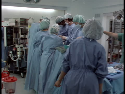 Following shot of a medical team performing surgery in an operating room.