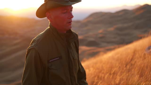ドゥルミトル国立公園の丘をハイキングする公園レンジャーのショットに続いて - 公園保安官点の映像素材/bロール