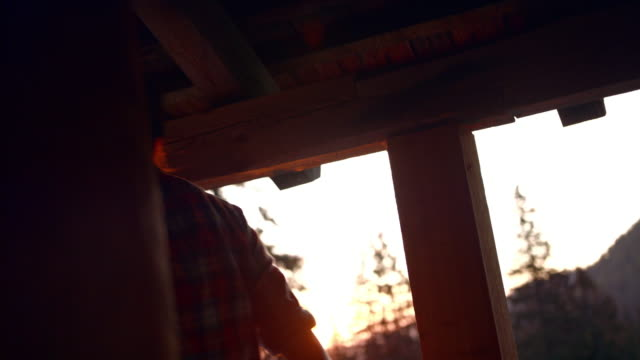 following shot of a young woman opening a cabin and exiting through the door at sunset - leaving stock videos & royalty-free footage