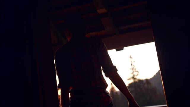 vidéos et rushes de tir suivant d'une jeune femme ouvrant une cabine et sortant par la porte au coucher du soleil - découverte