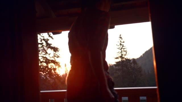 nach dem schuss einer jungen frau, die eine hütte öffnet und bei sonnenuntergang durch die tür geht - 25 29 jahre stock-videos und b-roll-filmmaterial
