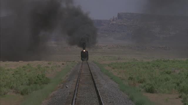 vídeos de stock, filmes e b-roll de following shot of an approaching train. - indo em direção