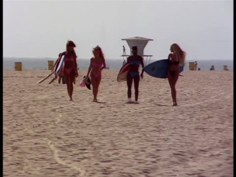 following shot of four women in bikinis and carrying surfboards. - venice beach stock videos & royalty-free footage