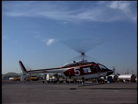 following shot of helicopter lifting off. - helicopter rotors stock videos and b-roll footage